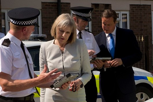 Prove who you are: Theresa May and David Cameron check the credentials of two police officers, to ensure they aren't illegal immigrants. No, not really - but don't be surprised if police checkpoints start appearing everywhere with people in peaked caps demanding your papers, just like in Nazi Germany during the 1930s and 40s!