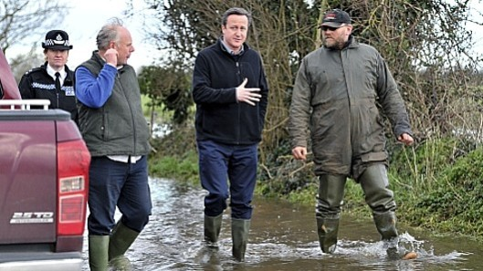 The Conservative response: David Cameron swans around the Somerset Levels in his wellies while local MP Ian Liddell-Grainger (second from left) tries to get a word in edgeways.