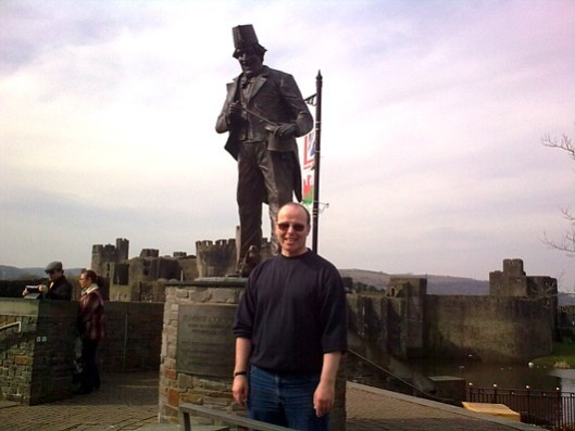 Standing in the shadow of a giant: Vox Political's Mike Sivier (front) at 'Cooper Corner', with Caerphilly Castle in the background.