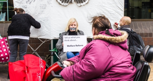 'People of Thurrock' in the making. Artist Melanie Cutler sits, silenced, while residents of Thurrock write their opinions of 'welfare reform' on the canvas.